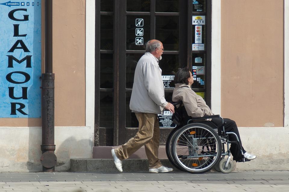 Persona in carrozzina con accompagnatore passeggiano sul marciapiede