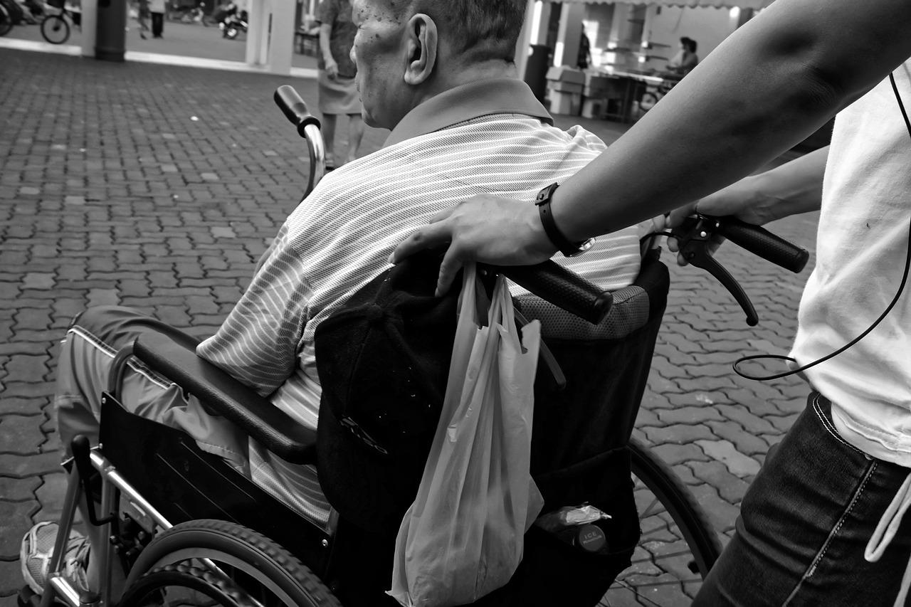 Un caregiver aiuta un signore anziano in sedia a rotelle. Foto in bianco e nero