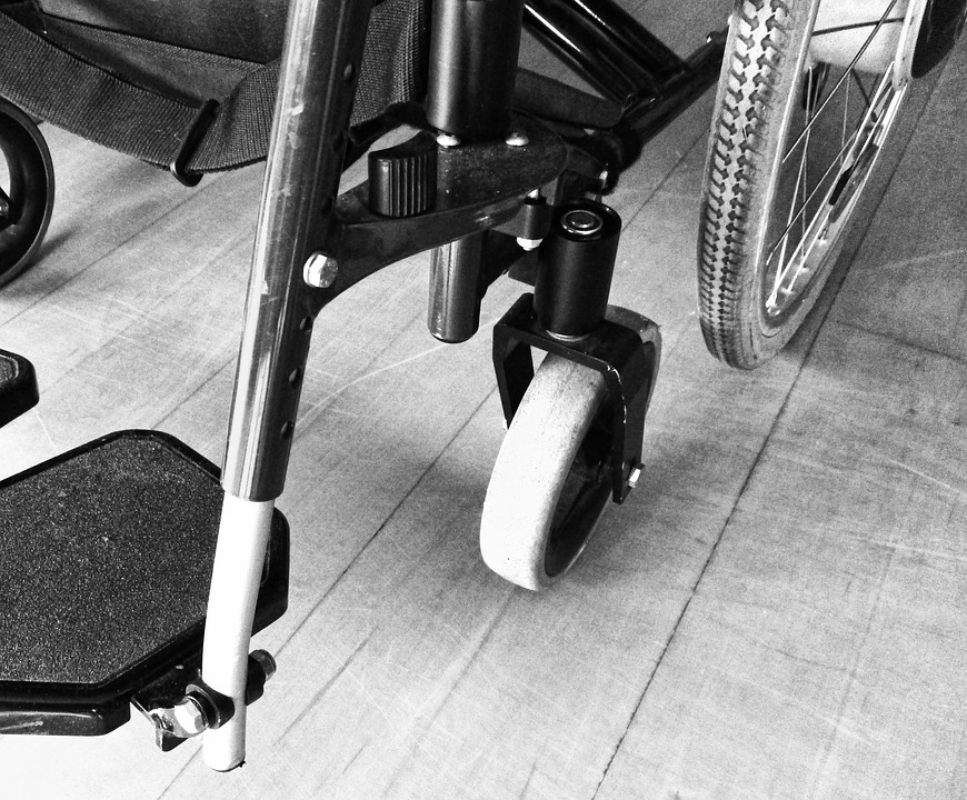 foto in bianco e nero di una ruota di una sedia a rotelle vuota