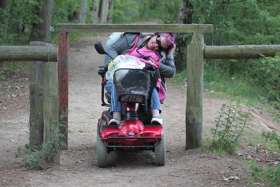 Ragazza con disabilità passa sotto una bassa recinzione in legno. Foto a colori