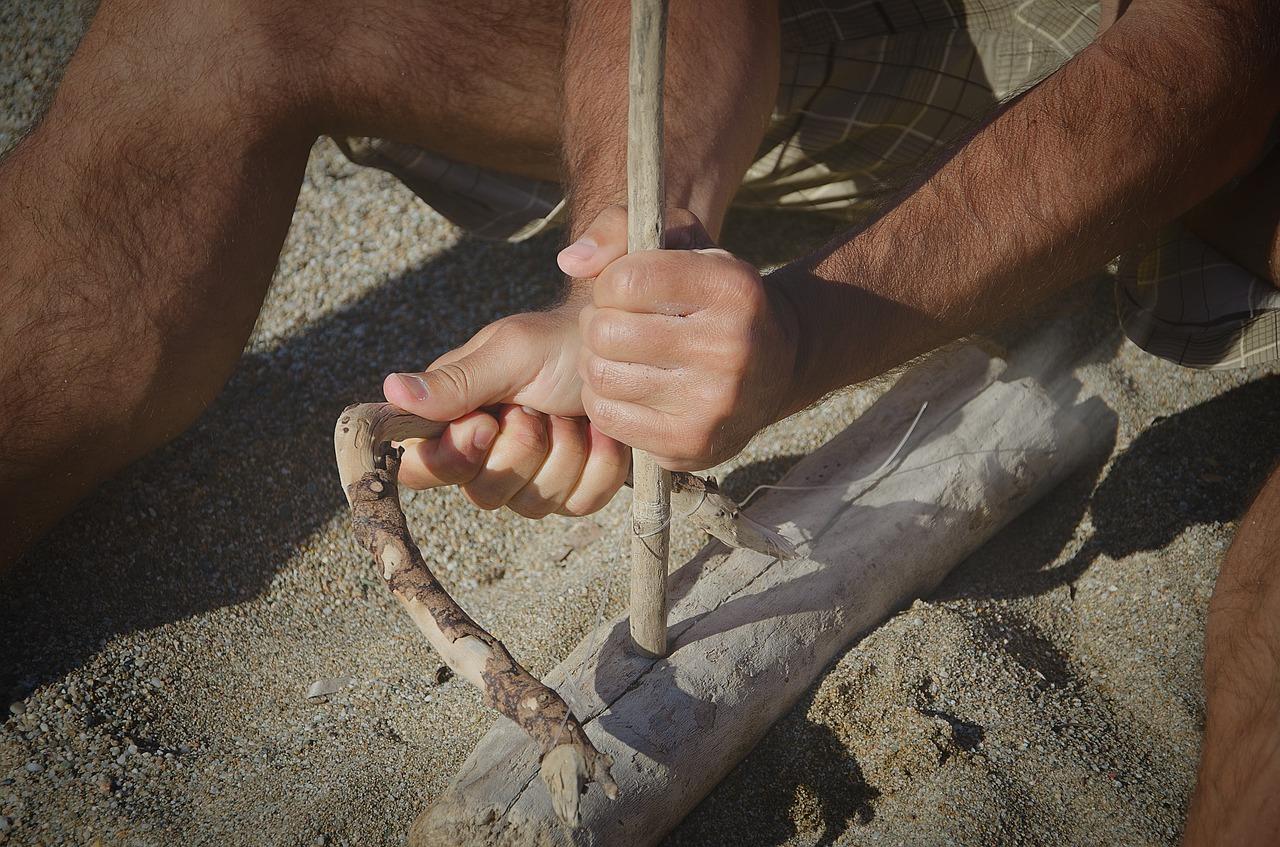 due mani che stringono un nodo attorno ad un tronco con una fune. Foto a colori.