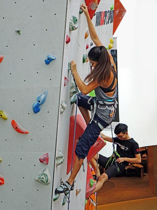 Una giovane ragazza intenta ad arrampicarsi su una parete