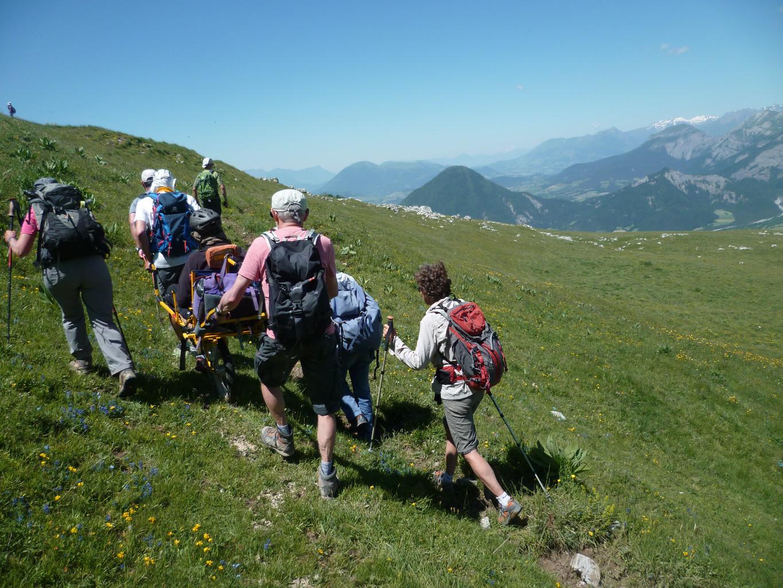 Persona con disabilità in joelette per raggiungere la vetta di una montagna