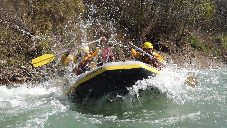 un team percorre un fiume con un gommone da rafting